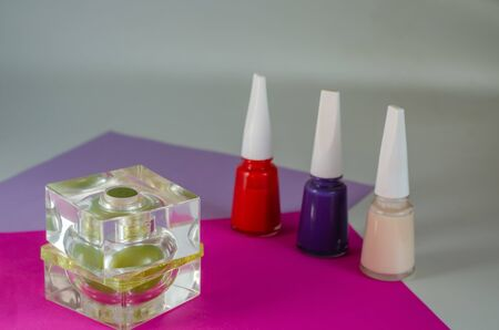 Three bottles of nail polish and one bottle of perfume. Gift for a scorned woman on the table. Selective focus. Close-up.