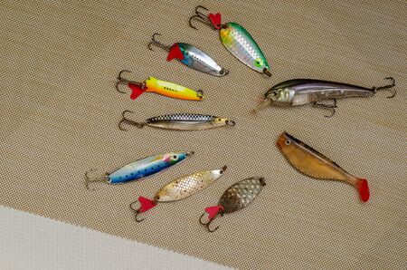 Used and new spinners, bobbler and silicone lures. Multi-colored fishing lures. View from above. Selective focus. Фото со стока