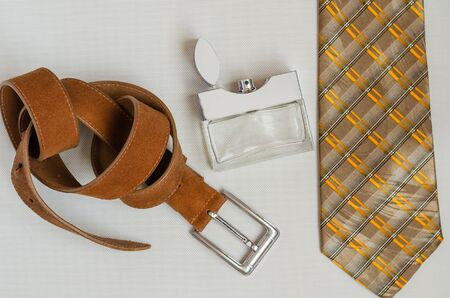 Silk Tie, perfume and leather trouser belt. A gift to her husband, lover, father, boyfriend. View from above. Selective focus. Vertical photo