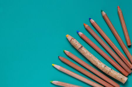 Wooden color pencils in the bottom corner. Place for designer text. View from above. Selective focus. Close-up. Standard-Bild