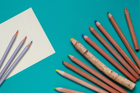 Group of multi-colored pencils on a turquoise background.View from above. Selective focus. Close-up. Archivio Fotografico