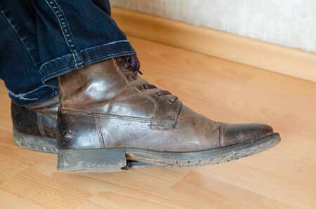 Dirty boots on a clean floor. Side view. Selective focus. Shooting inside the room. Stock Photo