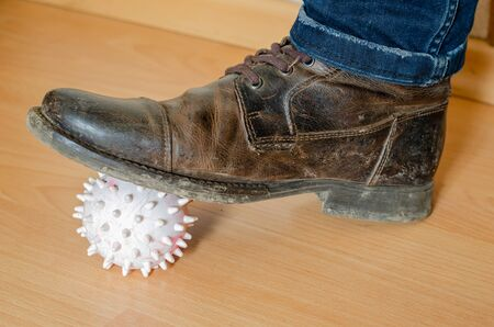 A light rubber ball with spikes is pressed to the wooden floor with a dirty boot. Close-up. Selective focus.