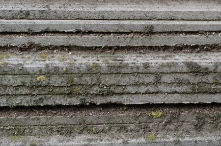 Outdated roofing material covered with moss and dirt. Side view. Eye level shooting. Close-up. Selective focus.