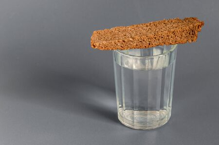 Full faceted glass of strong alcohol and bread on a gray background. Calm colors. Close-up. Selective focus.