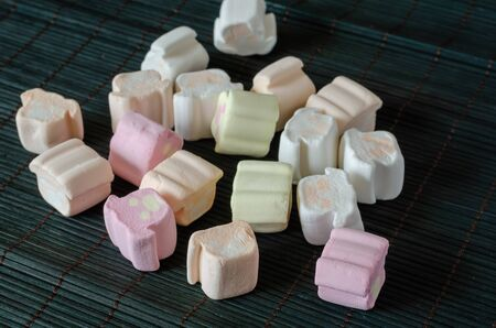 Colorful marshmallows on a dark background. Group of marshmallows on a bamboo substrate. Close-up. Selective focus.