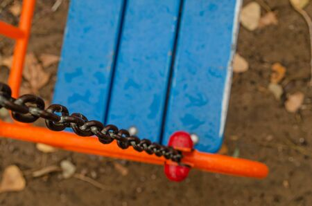 Empty swing for children on chains. Top view of a swing wet from the rain. Focus on chain links. Close-up. Selective focus.