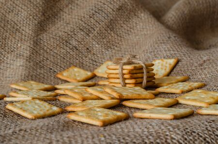 Salted crackers on burlap background. Crispy treats. Gluten free healthy foods. Eye level shooting. Selective focus. Close-up.