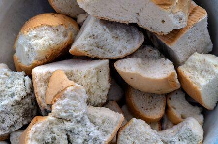 Pieces of bread with mold background. Pieces of spoiled white bread with traces of mold. Close-up. Selective focus. View from above.