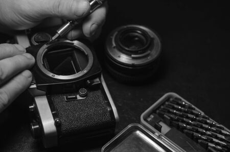 Disassembled vintage camera on a black table. Repair an old analog camera. The hand unscrews the lens mount screws with a screwdriver. Side view. Selective focus.
