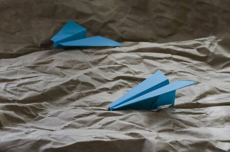 Two blue paper planes. Hand made by origami on a beige background. Crumpled paper simulates air currents. The concept of rivalry, competition. Selective focus. Close-up. Banco de Imagens