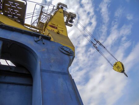 Port crane against the blue sky with clouds. Harbor crane with a lifting capacity of 20 tons lowers the hook into the hold of the vessel. The process of unloading metal. Commercial Sea Port. Shooting from the deck of the ship. View from the bottom up. Selective focus. Banque d'images