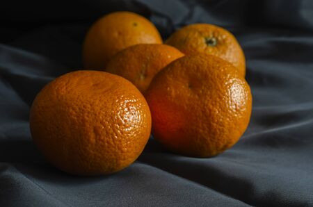 Ripe tangerines on black. A group of five tangerines close-up. Ripe citrus fruits in the peel. Eye level shooting. Selective focus.