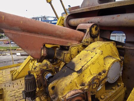 Fragment of a port crane close-up. The mechanism for controlling the angle of the cargo beam. Gearboxes with electric motors. View from the harbor crane assembly site. Repair and maintenance of port cranes. Selective focus. 版權商用圖片