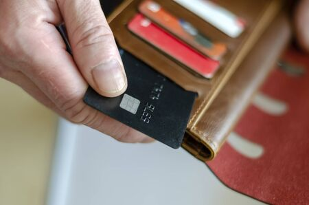 Hand takes out a bank card from the wallet. Adult man holds a black bank card. Payment for goods in the store. Selective focus. Close-up. Banque d'images - 144122048