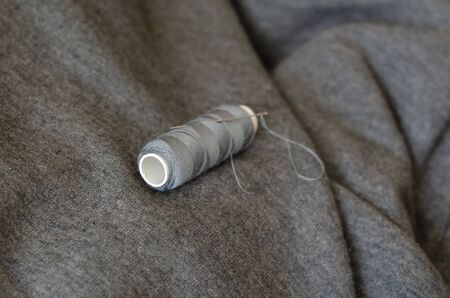 Spool of gray thread with a needle. Tailor's manual tool on gray fabric. Craft tailor or seamstress. Selective focus. Close-up.