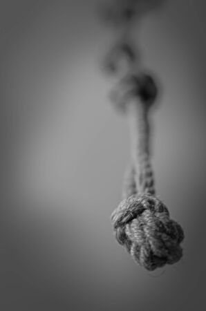 Jute rope hanging from above with knots. Rope with rough knots in a receding perspective. The concept of striving up for a better or achieving a goal. Selective focus. Close-up. Shooting from the bottom up.