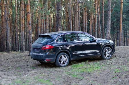 Nikolaev, Ukraine, April 9, 2020: Porsche Cayenne in the forest. Premium black SUV in the morning pine forest. Spring morning before dawn.