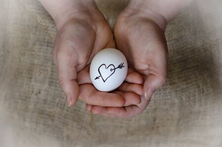 The symbol of love is painted on a chicken egg. Hands holding a raw egg with a heart and arrow symbol. Cherish the love. Top view at an angle. Close-up. Selective focus.