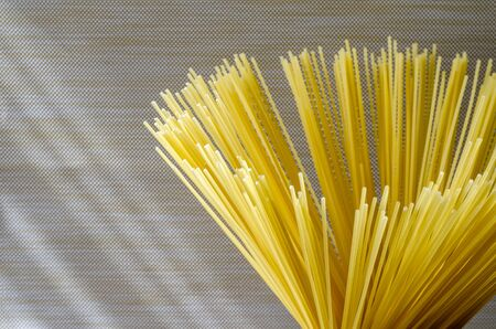 Spaghetti on a beige background. A bunch of spaghetti close-up. Group of dry spaghetti. Unprepared pasta. Side view. Selective focus.