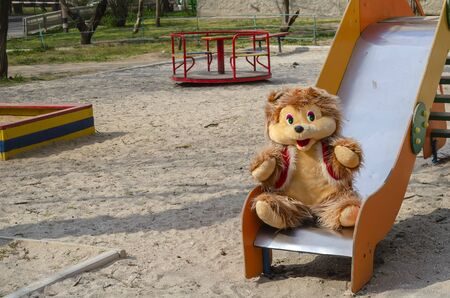 Big teddy bear in a deserted playground. A smiling bear sits on a children's slide. Spring sunny day on the playgrounds without people. Self-isolation, quarantine. Selective focus.