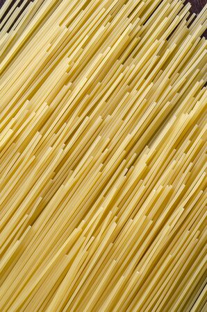 Raw spaghetti background. Unprepared spaghetti on a dark wooden table. Simple traditional homemade food. Shooting from above at an angle. Selective focus. Close-up