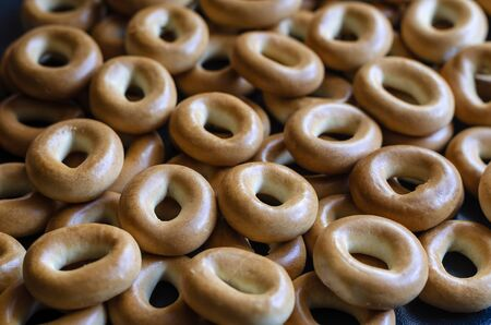 Traditional round bagels background. A bunch of sweet treats for tea. Eye level shooting. Close-up. Selective focus.