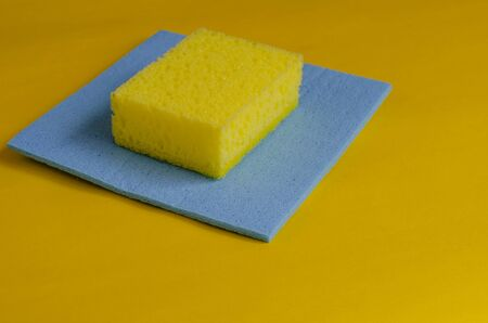 Kitchen sponge and blue cleaning napkin on yellow. Accessories for washing dishes and cleaning. Commercial cleaning company. Selective focus. Close-up.