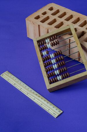 Brick, wooden abacus and ruler. Single brick and stationery on a blue background. Construction industry, calculation of balance and building materials. Folk proverb. Selective focus.