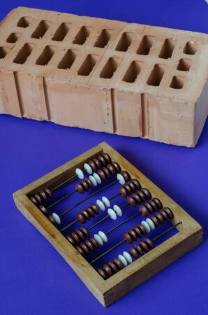 Brick and wooden abacus on a blue background. New red brick and screw wooden abacus. Construction topics. Close-up. Selective focus.
