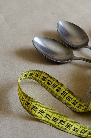 Tailor meter and two tablespoons. Metallic spoons with a yellow meter on beige. Office overeating. Fighting Overweight. Side view. Selective focus.