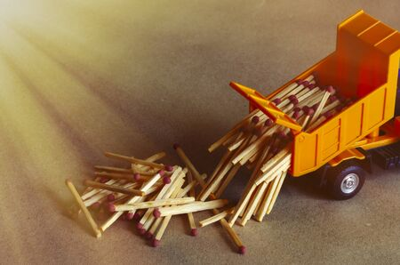 A yellow toy dump truck spills matches. A toy truck unloads a full body of wooden matches. Creative industrial background. Logistic topics. Selective focus.