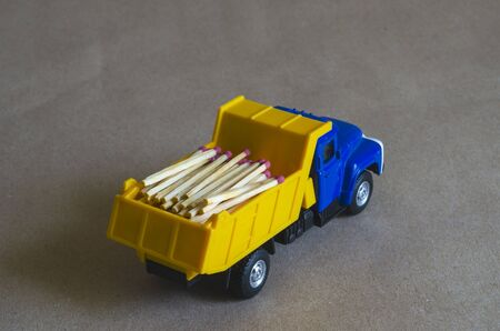 A yellow dump truck with a blue cab carries matches. Toy truck with a full body of wooden matches. Creative industrial background. Logging and logistics. Selective focus.