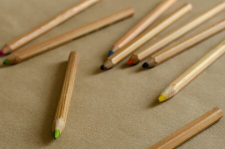 Color pencils on a beige background. Set of wooden used pencils randomly on the table. Eye level shooting. Selective focus. Imagens