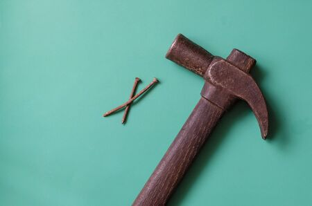 Vintage hammer and two rusty nails on a turquoise background. Old hammer with a pair of nails. Place for text. Flat lay.