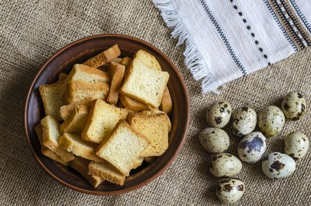 Raw quail eggs and a bowl with croutons. A group of fresh eggs and a serving of crispy croutons on burlap. Ingredients for the salad. Close-up. Selective focus. Banco de Imagens