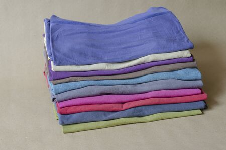 Ten t-shirts of different colors. Set of multi-colored t-shirts. A stack of trendy t-shirts closeup. Comfortable casual wear. Selective focus.