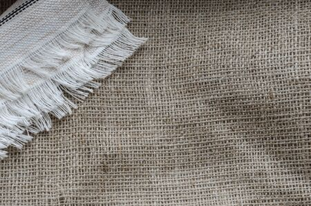 Cloth napkin with fringe on burlap. Linen white napkin on top of coarse fabric. Multitask background from natural fabrics. View from above. Place for text.