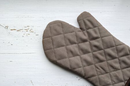Brown kitchen quilted glove on a white wooden background. Wooden background with cracked paint. Place for text. View from above.
