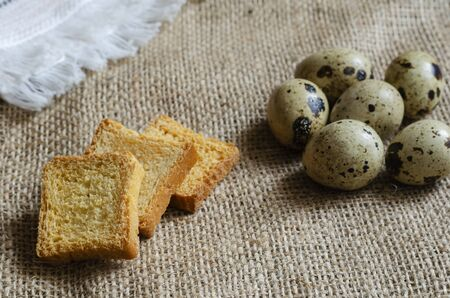Square croutons and raw quail eggs on burlap. Three small croutons and a group of eggs. Still life in a rural style. Top view at an angle. Selective focus