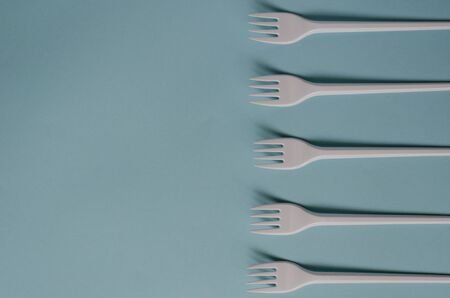 Abstract background with disposable cutlery. Plastic forks on a light blue background. A group of White disposable forks in a line. Serving, food industry. View from above. Selective focus. Фото со стока