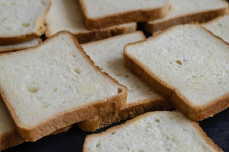 Sandwich bread background. Rectangular pieces of bread pile on the table. Angled side view. Close-up. Selective focus.