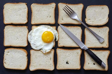 Creative background with fried egg and toast bread. A single fried chicken egg with a fork and knife on a background of pieces of bread. Breakfast at the roadside cafe. Traveling by car, tourism.