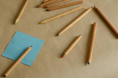 Plain background with a set of pencils and a blank stationery. Square sheet of paper and color pencils. A set of used pencils randomly on the table. Eye level shooting. Selective focus. Close-up.