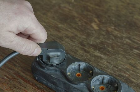 Incorrect disconnection of the electrical plug from the extension cord. Incorrect hold of the electric plug in the hand. A worker disconnects a power tool from a black extension cord on a wooden table. Electrical safety.