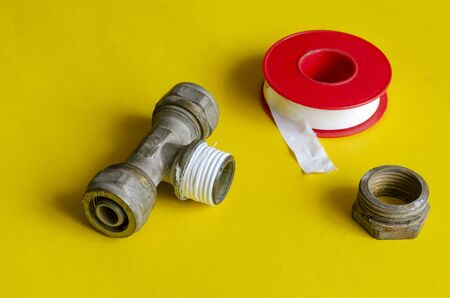Water tee splitter, nut and sealing tape on a yellow background. The process of repairing the water supply. Plumber or plumbing service. Close-up. Selective focus.