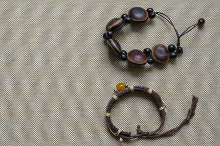 Handmade bracelets for women on a beige textured background. Brown bracelets made of leather and wood close-up. Free space for text. View from above.