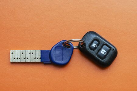 Chipped door key with remote control on an orange background .. Innovative key with a unique secret combination. Modern technologies for the protection of private property and personal property. Copy space.