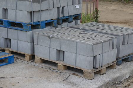 New road curbs on the pallet. Large gray curbs on wooden pallets. Tied with plastic bondage tape. Materials for road construction. Outside Without people. Stock Photo