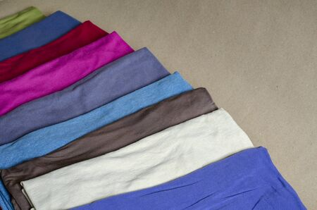 Set of multi-colored t-shirts. T-shirts laid out for demonstration in a line. Comfortable casual wear. Close-up. Selective focus. Banco de Imagens
